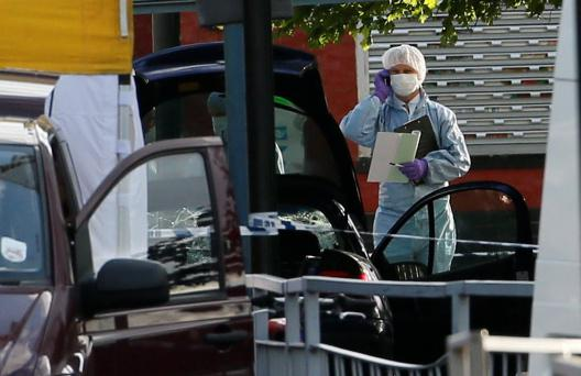 A police forensics officer investigates a car at a crime scene where one man was killed in Woolwich, southeast London May 22, 2013. British Prime Minister David Cameron has called a meeting of his government's emergency Cobra security committee after the killing of a man in south London, his office said on Wednesday. REUTERS/Stefan Wermuth (BRITAIN - Tags: CRIME LAW POLITICS)