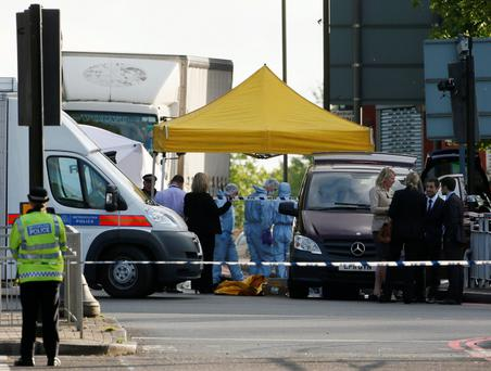 Police forensics officers investigate a crime scene where one man was killed in Woolwich, southeast London May 22, 2013. British Prime Minister David Cameron has called a meeting of his government's emergency Cobra security committee after the killing of a man in south London, his office said on Wednesday. REUTERS/Stefan Wermuth (BRITAIN - Tags: CRIME LAW POLITICS)