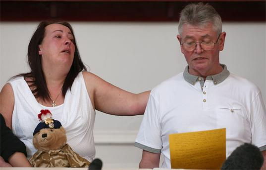 The mother of murdered soldier Lee Rigby, Lyn, comforts her husband and stepfather to Lee, Ian Rigby, as he reads a family statement to the media