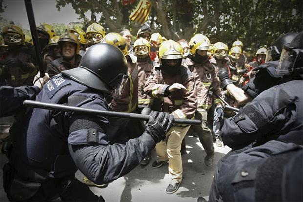 Riot police charge at firefighters during a protest against austerity measures in front of the Catalunya Parliament in Barcelona, Spain.