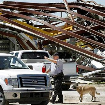 A police officer offers directions to a driver leaving this heavily damaged supply yard for Cactus Drilling Company
