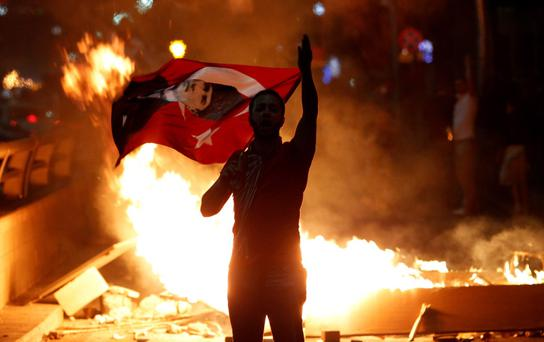 An anti-government protester holds a Turkish national flag with a portrait of Mustafa Kemal Ataturk, founder of modern Turkey, on it during a demonstration in Ankara