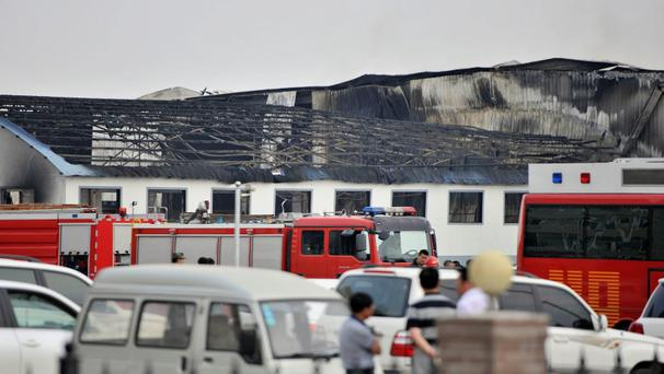 Rescue workers and fire trucks are seen outside a site of a fire, at a poultry slaughterhouse in Dehui, Jilin province