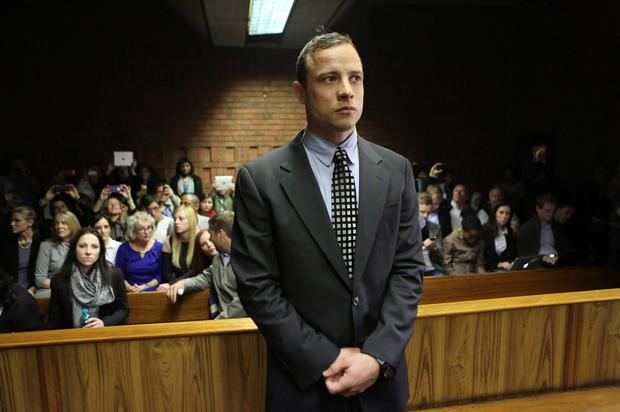 Oscar Pistorius enters the dock before in court proceedings at the Pretoria Magistrates court