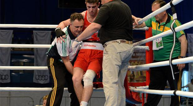 Joe Ward is assisted by Ireland coach Billy Walsh after sufffering a knee injury