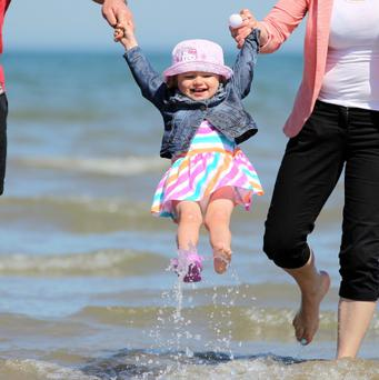 Two-year-old Victoria Klzyz from Lucan swings through the water at Portmarnock with help from her mum and dad