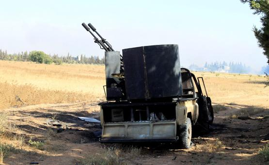 A damaged military vehicle used by the Free Syrian Army is seen after heavy fighting against the forces of Syrian President Bashar al-Assad and Lebanon's Hezbollah in the al-Barak area near Qusair town on May 31