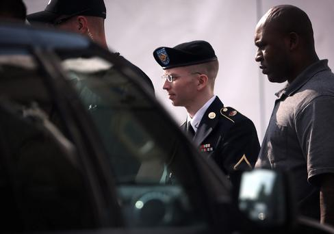 US Army Private First Class Bradley Manning (C) is escorted as he leaves a military court for the day June 3, 2013 at Fort Meade in Maryland