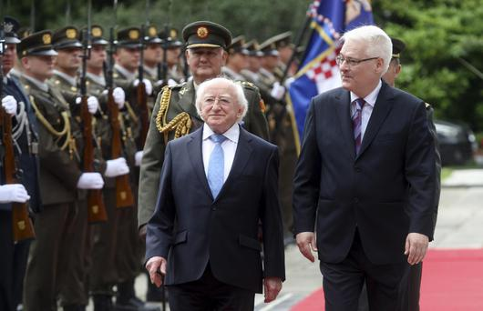 Ireland's President Michael Higgins, left, reviews Croatian honor guards with his Croatian counterpart Ivo Josipovic, right, in Zagreb, Croatia