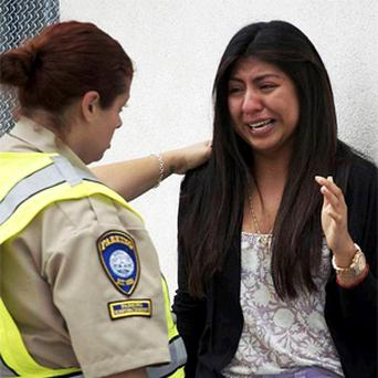 Priscilla Morales, who was in the library at Santa Monica College where a gunman who allegedly killed at least six people with an assault-style rifle was shot to death in a gunfight with police, cries as she is consoled by a parking enforcement officer.