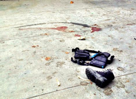 The equipment of a man believed to be the suspect in a shooting incident at Santa Monica College lies on the footpath after he was shot.