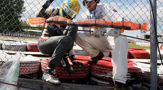 Sauber Formula One driver Esteban Gutierrez of Mexico climbs through the fence after crashing during the Canadian F1 Grand Prix
