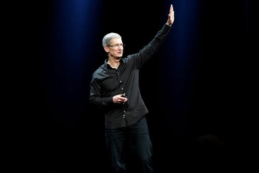 Apple CEO Tim Cook waves to the crowd during the Apple Worldwide Developers Conference (WWDC) 2013 in San Francisco, California