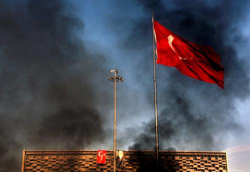A huge Turkish flag is obscured by black smoke from burning barricades during clashes between police and anti-government protesters in Istanbul's Taksim Square