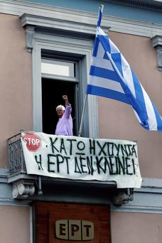 An employee raises his arm from a balcony of the studio of state broadcaster ERT in Athens.