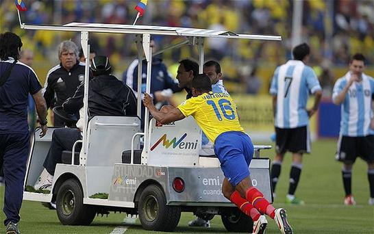 The injured Javier Mascherano is carted off the pitch. Shortly after he was sent off for kicking the driver of the motorised vehicle. Photo: AP