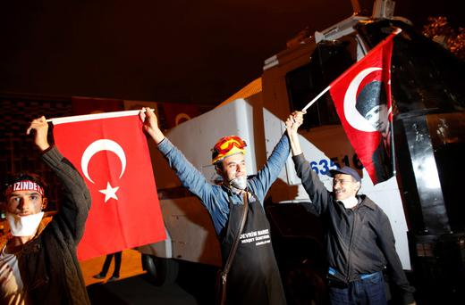Demonstrators, holding Turkish flags, one of which bears a portrait of Mustafa Kemal Ataturk (R), founder of modern Turkey, form a human chain in front of security forces