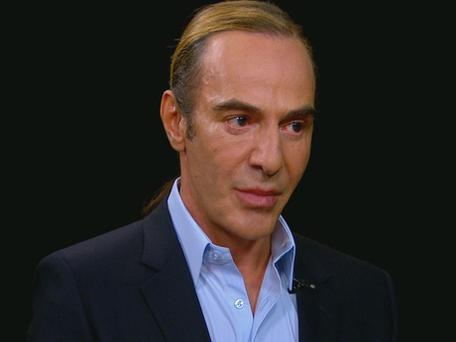 Galliano wears a simple pale blue shirt and navy jacket while looking somewhat drawn and downcast.