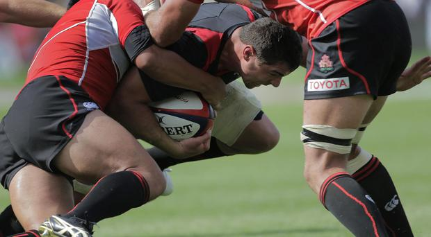Andries Pretorius of Wales, is tackled by Japan's Shota Horie and Michael Broadhurst