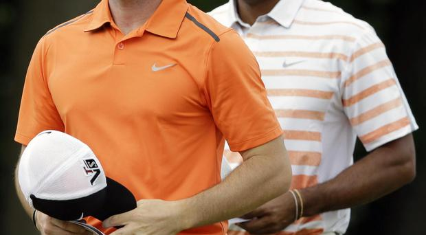 Rory McIlroy and Tiger Woods walk across the 10th green after putting during the second round of the U.S. Open