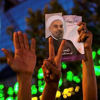 Supporters of Hassan Rowhani hold a picture of him as they celebrate his victory in Iran's presidential election.