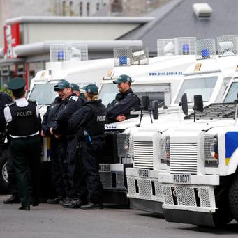 Police officers gather next to armoured land rovers in Enniskillen, in Northern Ireland. REUTERS/Andrew Winning