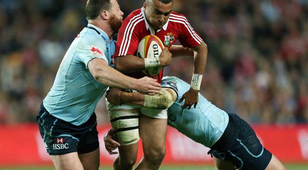 Simon Zebo gets tackled by NSW Waratahs' Paddy Ryan (left) and Tom Carter