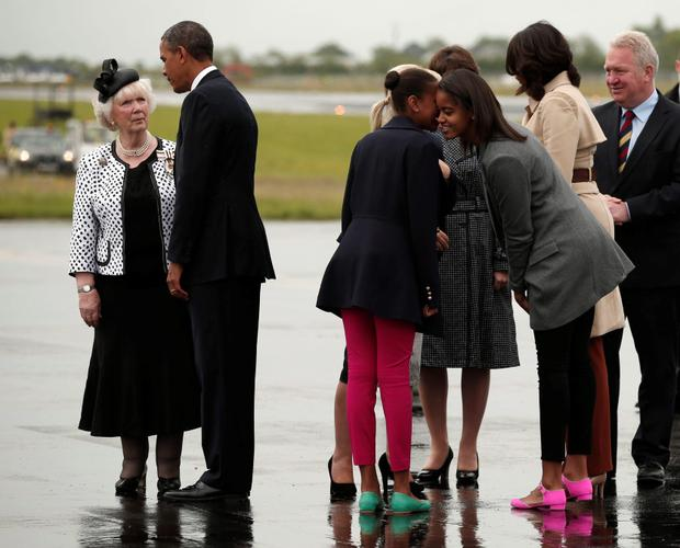 Sasha and Malia Obama chat as U.S. President Barack Obama is greeted upon their arrival on Air Force One in Belfast.