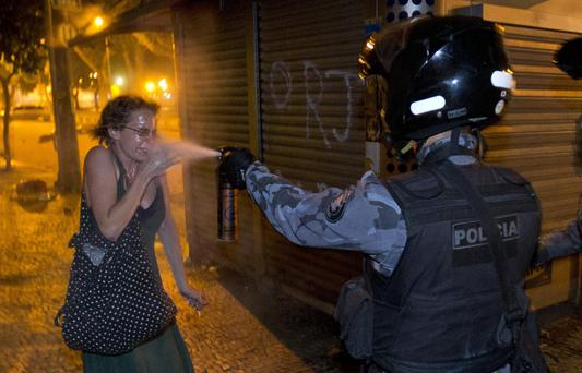 A military police peper sprays a protester during a demonstration in Rio de Janeiro, Brazil, Monday, June 17, 2013.