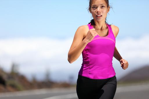woman runner training for marathon. Female runner in sporty pink tank top jogging on mountain road. Beautiful young mixed race Asian Caucasian female fitness model outside.