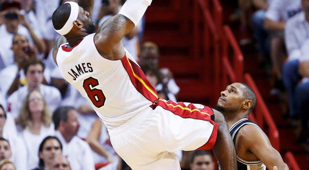 Miami Heat's LeBron James takes a fade-away jumper while being guarded by Boris Diaw