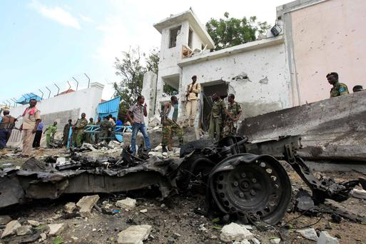 Security agents stand near the scene of a suicide bomb attack outside the United Nations compound in Somalia's capital Mogadishu