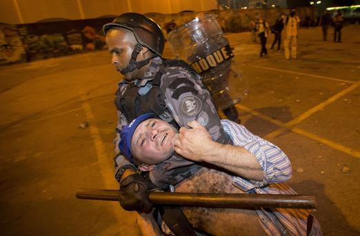 Military police detain a man during an anti-government protest in Rio de Janeiro, Brazil, Thursday, June 20, 2013.