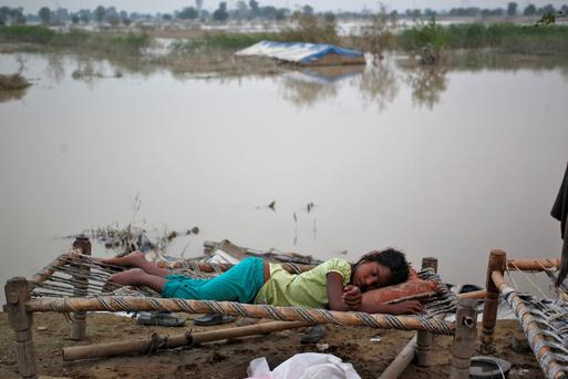 A displaced girl sleeps outside her makeshift tent at a camp by the roadside after a rise in the waters of the river Yamuna after heavy rains in New Delhi June 21, 2013