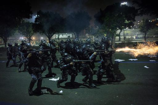 Anti riot police officers fire rubber bullets after clashes erupted during a protest against bus fare price hikes June 20, 2013 in Rio de Janeiro, Brazil