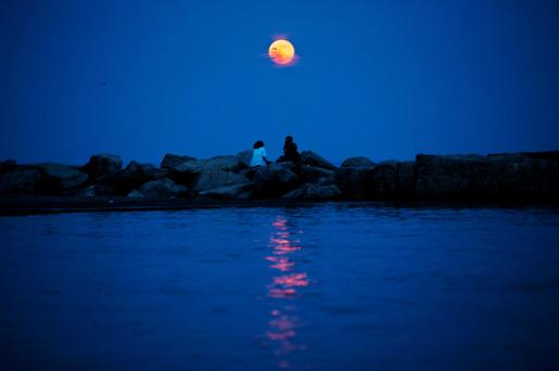The moon is seen in an abnormally red colour as it rises in the Toronto Beaches, June 23, 2013. The largest full moon of the year called the