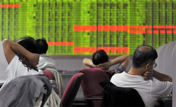 Investors sit in front of an electronic board showing stock information at a brokerage house in Zhongshan, Guangdong province, China