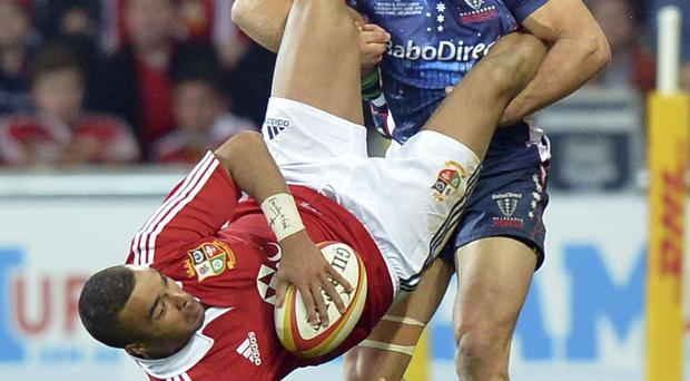 British and Irish Lions Simon Zebo is tackled heavily by Lachlan Mitchell