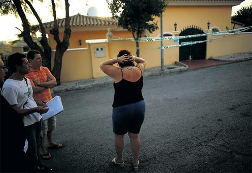 A friend of the family, identified only as Carmen, reacts outside the house where three bodies were found in Mijas, Spain