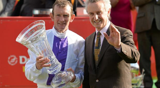 Jockey Kevin Manning and trainer Jim Bolger celebrate after they sent out Trading Leather to win the Dubai Duty Free Irish Derby