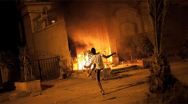 An Egyptian protester attacks Muslim Brotherhood headquarters in the Muqattam district in Cairo