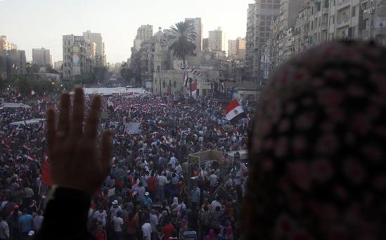 A woman looks through the glass of a pedestrian bridge overlooking an anti-Egyptian President Mohamed Mursi protest at a main square in Alexandria, July 1, 2013