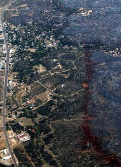 An aerial view of a strip of fire retardant near Yarnell, Arizona separating the burned area from the green area is seen on July 1, 2013