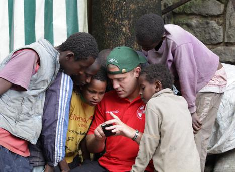 Ian Madigan shows some street children a photo he took of them on his smartphone as he visited a GOAL project for street children in Addis Ababa