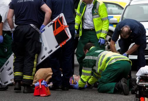 The man lies on street attended to emergency services (Picture: Mark Condren)