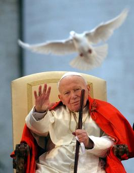 In this April 10, 2003 file photo Pope John Paul II looks at a white dove released in honor of his repeated calls for peace by Roman youths in St. Peter's Square at the Vatican.