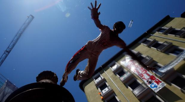A reveller jumps from a fountain at the Plaza de Navarreria as he is sprayed with water during the start of the San Fermin festival in Pamplona July 6, 2013. REUTERS/Susana Vera (SPAIN - Tags: SOCIETY)