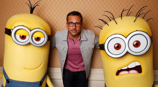 Actor Steve Carell poses with two life-size minion characters while promoting his movie