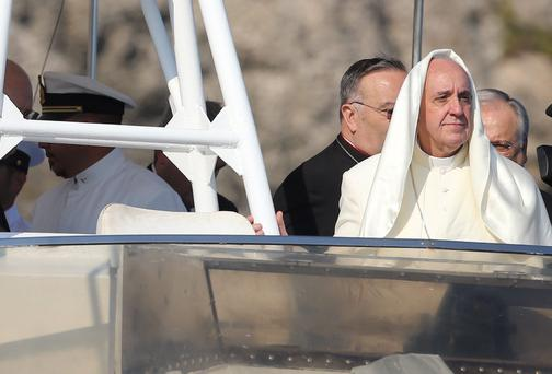 A gust of wind lifts up Pope Francis' mantle as he stands onboard a boat at Lampedusa Island, southern Italy, July 8, 2013