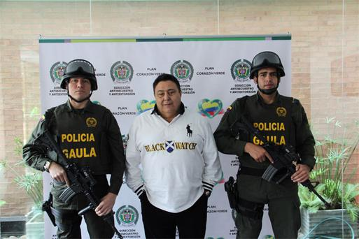 Colombian Police stand guard next to suspected drug lord Roberto Pannuzzi in Bogota